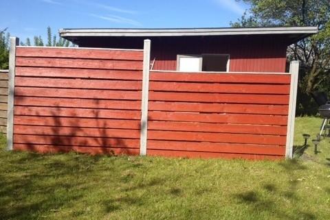Maling af hegn ved grund rødt